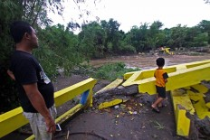 The remains of a bridge destroyed by flood waters in Blawong village in Jetis district, Bantul regency, on Nov. 28. Villagers have been forced to take a longer route to reach the other side of the river. JP/Aditya Sagita