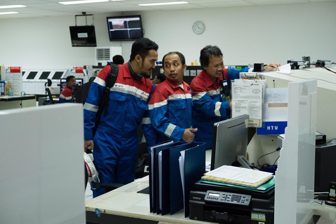 Coordination: Three workers engage in a discussion in the control room prior to handing over their work shifts. JP/ Jerry Adiguna