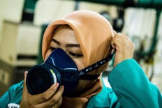 Ready to go: Researcher Shindy Dila Putri puts on a safety mask before starting her daily activities in the water control laboratory. JP/ Jerry Adiguna