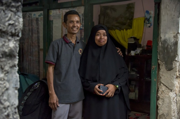 This photograph taken on October 24, 2017 shows Sriyono (L), who suffers from asbestosis - scarring of the lungs from breathing in asbestos fibres, posing with his wife in front of his house in Cibinong, West Java province.