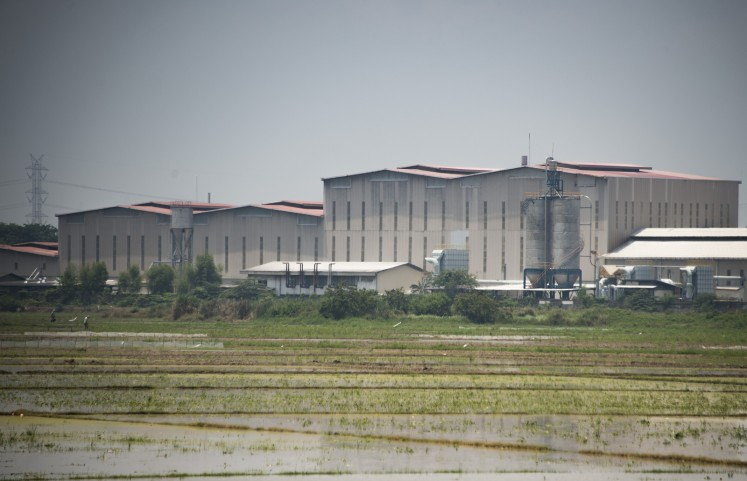 This photograph taken on October 24, 2017 shows paddy fields surrounding a factory which makes asbestos products in Cikarang, West Java province.