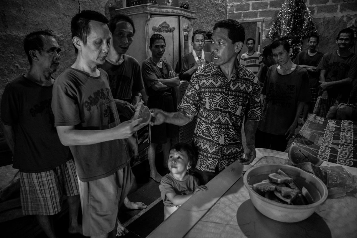 One for one: Imanuel Talan distributes slices of watermelon to residents while his daughter, 2-year-old Senandung Nathania Talan, watches. JP/Seto Wardhana