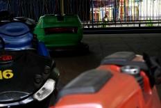 A boy peers inside an empty bumper car arena. JP/Maksum Nur Fauzan