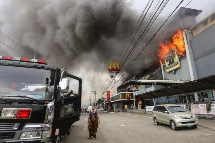 This photo taken on December 23, 2017 shows a firefighter standing in front of a burning shopping mall in Davao City on the southern Philippine island of Mindanao. Thirty-seven people were believed killed in a fire that engulfed a shopping mall in the southern Philippine city of Davao, local authorities said on Dec. 24.