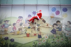 A man dressed as a Santa Claus descends from the roof of the Pediatric Clinic in Ljubljana, on December 19, 2017. Men dressed as a Santa Claus descended from the roof of Pediatric Clinic to entertain the children and bring them presents. AFP/Jure Makovec