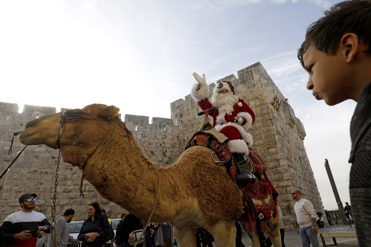 A man dressed as Santa Claus rides a camel along Jerusalem's Old City Ottoman walls on December 21, 2017. AFP/Gali Tibbon