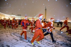 Participants wear Santa Claus costumes as hey take part in the Christmas race at Dvortsovaya square in Saint Petersburg, on December 23, 2017. AFP/Olga Maltseva