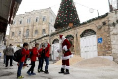 A man dressed as a Santa Claus greets children near a giant Christmas tree, as he walks in the Christian Quarter of the old city of Jerusalem on December 20, 2017. AFP/Gali Tibbon