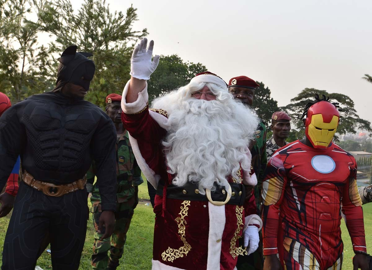 People dressed as (L-R) Batman, Santa Claus and Iron Man   walk at the presidential palace in Abidjan on December 23, 2017, during a Christmas event organised by the Children of Africa Foundation. The event, organised by Ivory Coast's first lady and president of the Children of Africa Foundation, welcomed 3000 children from Abidjan and Agboville. AFP/Sia Kambou