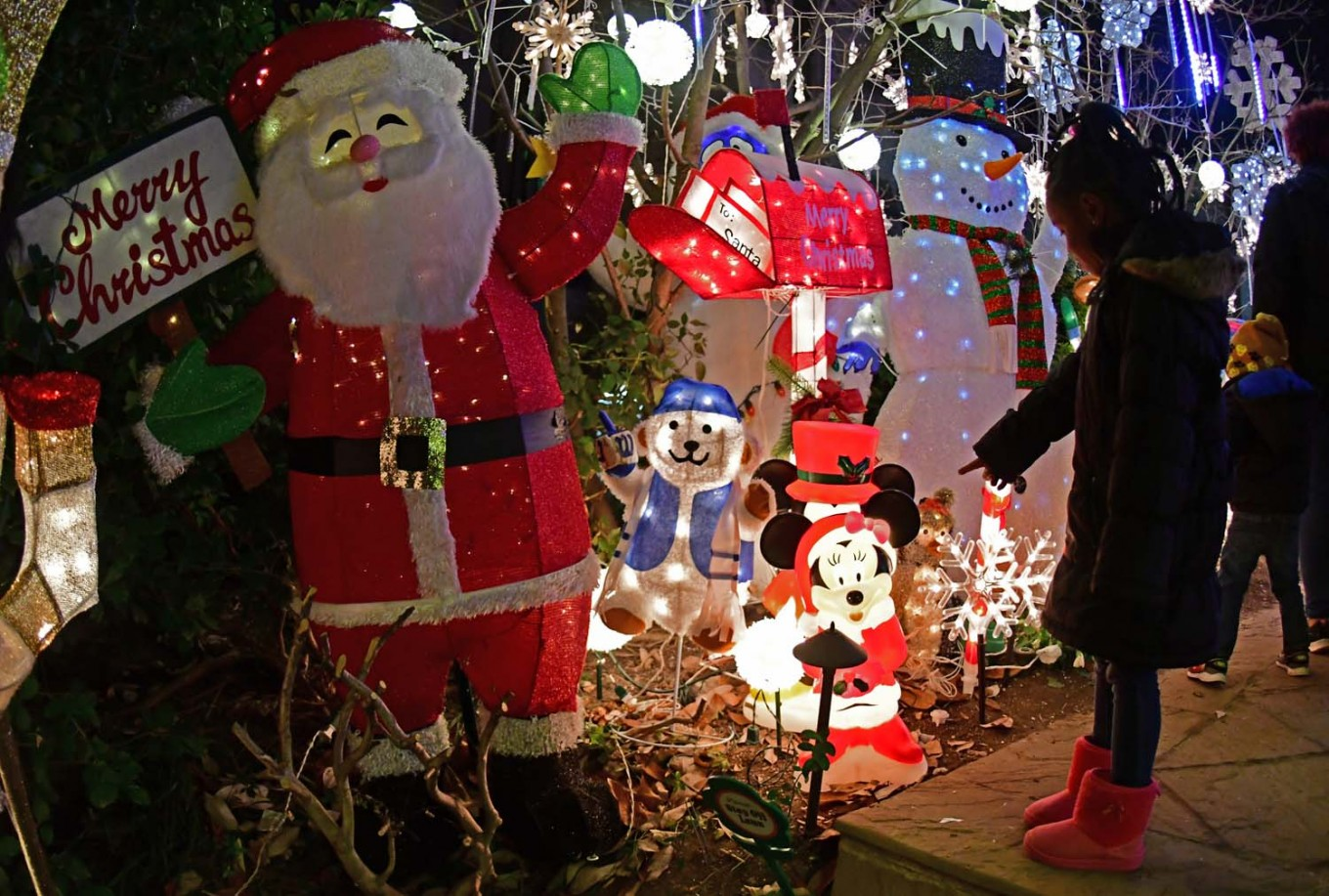 """A girl points at a Minnie Mouse on December 22, 2017 at """"Arbo & Santa's Dog Park"""", a residential front yard full of Christmas decorations set up by """"Mr. Holiday"""", a resident of Washington, DC who celebrates every single holiday of the year. AFP/Eva Hambach"""