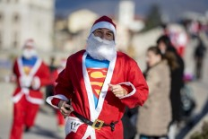 A man dressed as Santa Claus with Superman t-shirt takes part in the traditional New Year's Santa Claus race in Skopje, on December 24, 2017. AFP/Robert Atanasovski