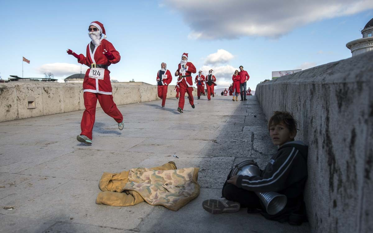 A child plays the tambourine while men dressed as Santa Claus take part in the traditional New Year's Santa Claus race in Skopje, on December 24, 2017. AFP/Robert Atanasovski
