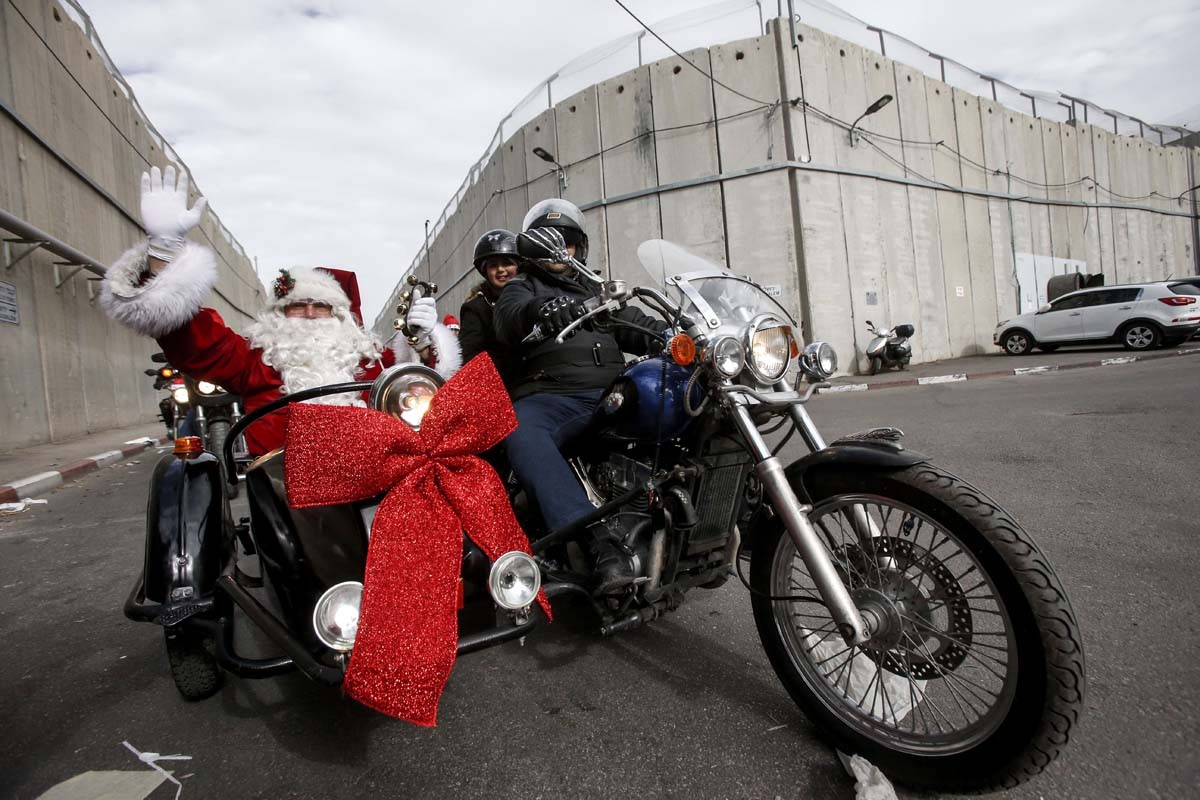 A man dressed as Santa Claus waves to people as he rides in the sidecar of a motorcycle, ahead of the motorcade of Archbishop Pierbattista Pizzaballa, Apostolic Administrator of the Latin Patriarchate of Jerusalem, while crossing through an Israeli checkpoint in the controversial separation barrier to attend Christmas eve celebrations in the West Bank city of Bethlehem December 24, 2017. AFP/Hazem Bader