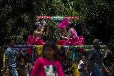 Girls – who have been dressed up – are being carried from their houses to the nearest field for the Henauka Wowine coming of age celebration. Antara/Rosa Panggabean