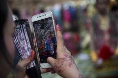 A family member captures the proud moment with her mobile phone. Antara/Rosa Panggabean