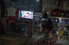 Nadira is watching Doraemon cartoon tv show. Antara/Rosa Panggabean