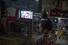 Nadira is watching Doraemon cartoon tv show. Antara/Rosa Panggabean