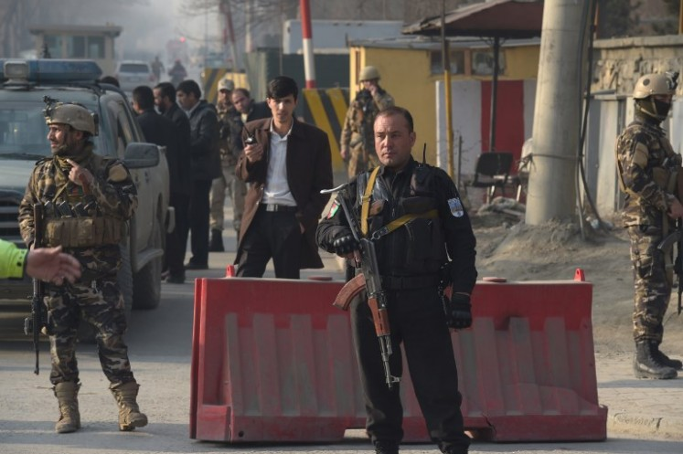 Afghan security personnel keep watch near the site of a suicide attack in Kabul on December 25, 2017. A suicide attacker on foot blew himself up near a compound belonging to the Afghan intelligence agency in Kabul on December 25, killing six civilians, officials said.