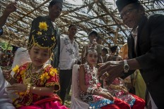 The girls take part in the landa futa procession in which a religious leader will grease turmeric in the girls' forehead and feet and pray for their future. Antara/Rosa Panggabean
