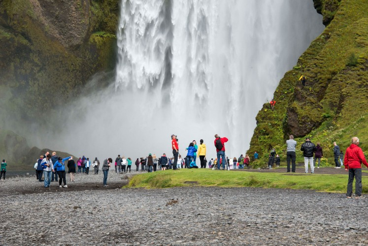Crowds form in front of the waterfall at Skogar, in Iceland.