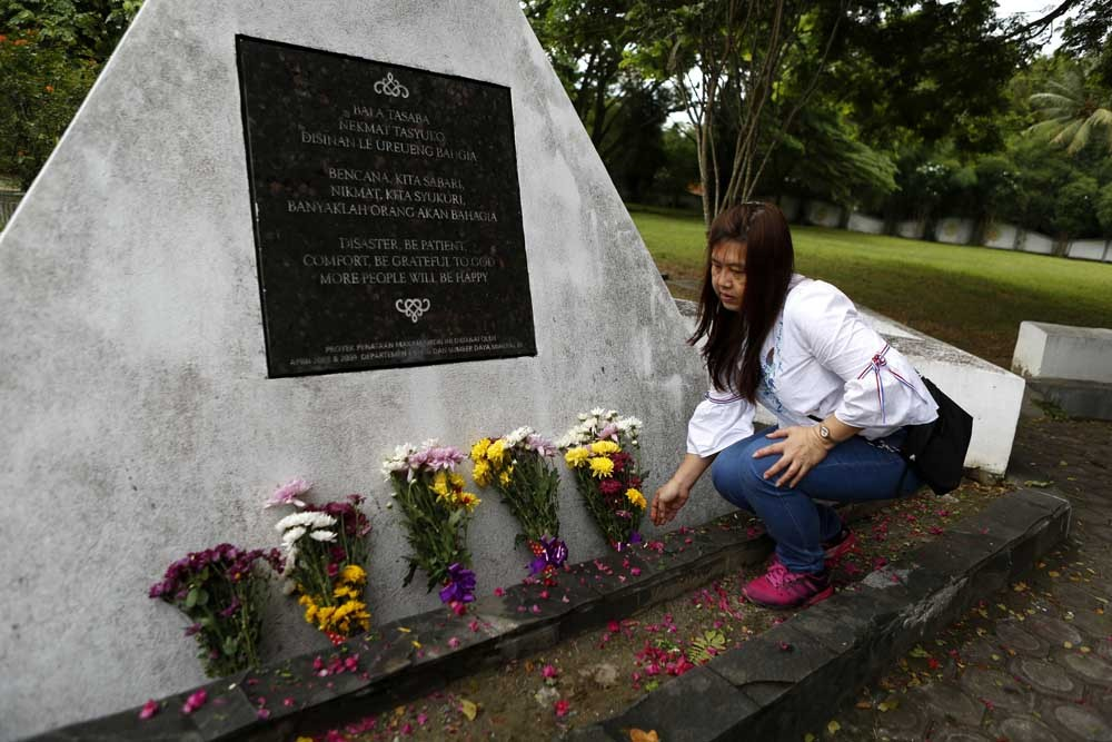 An Acehnese places a flower bouquet at the mass burial site during the commemoration of the tsunami in Banda Aceh, Dec. 26, 2017. JP/Hotli Simanjuntak