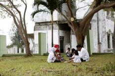 A family prays at the burial site during the tsunami commemoration. JP/Hotli Simanjuntak