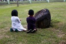 Two children pray at the mass burial site. JP/Hotli Simanjuntak