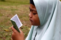 A young girl reads the Yassin verse while praying at the burial site. JP/Hotli Simanjuntak