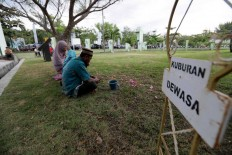 A man leads his family to pray at the burial site. JP/Hotli Simanjuntak