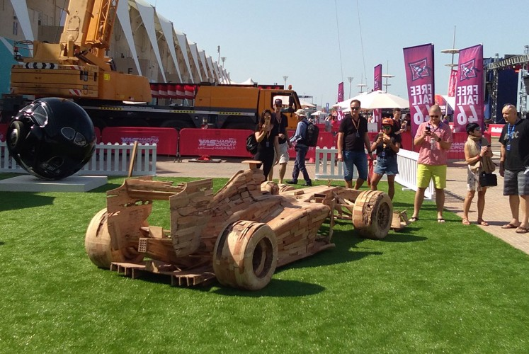 F1 fans observe Noor's 'Got Wood,' a wooden replica of an F1 racing car.