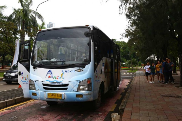 Passengers wait for the Wara Wiri bus in Ancol Taman Impian, North Jakarta, on Thursday, Dec. 22, 2017.
