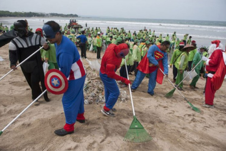 Cleaners dressed up in superhero costumes tidy up Kuta Beach, Bali.