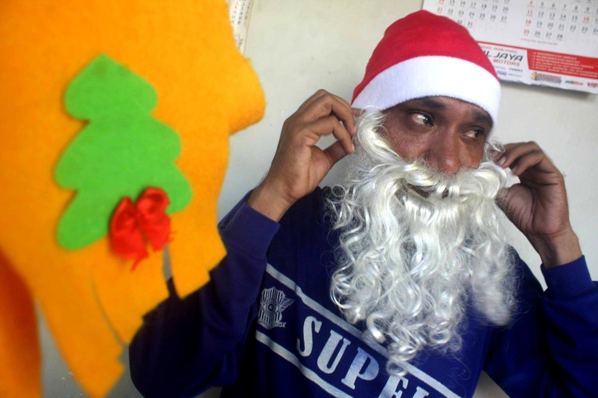 He puts on his fake Santa beard. JP/Maksum Nur Fauzan
