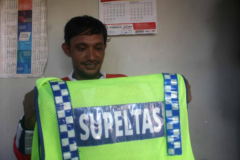 He folds up his Supeltas (volunteer traffic warden) vest. JP/Maksum Nur Fauzan