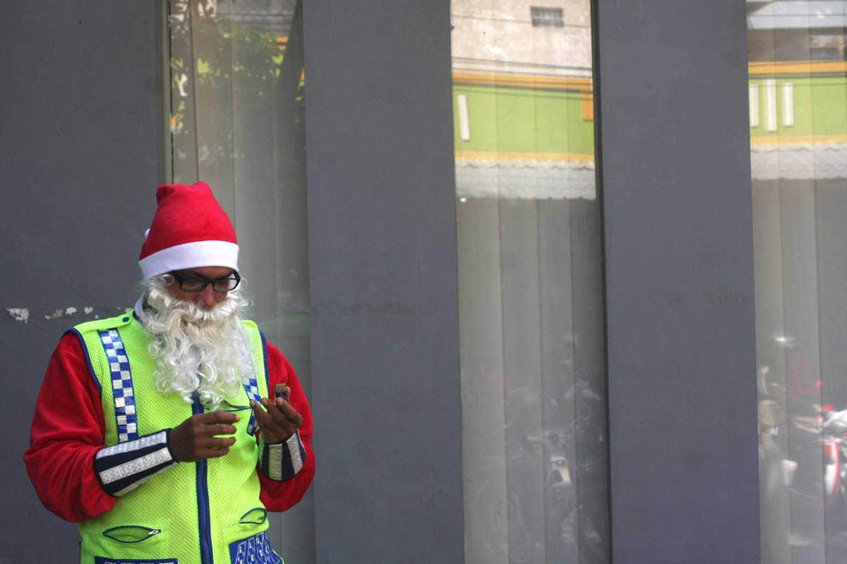 Dressed as Santa Claus, Marthins Hidungoran normally prays before he voluntarily directs traffic in Surakarta, Central Java, on Christmas Day. JP/Maksum Nur Fauzan