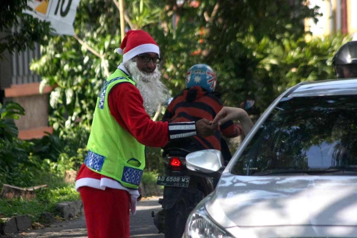 Motorists give their small change to him. JP/Maksum Nur Fauzan