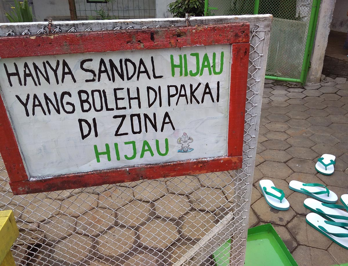 """A warning board saying """"Only green slippers are allowed in the green zone"""" is put on the entrance of the green zone in the farms' area. JP/Ganug Nugroho Adi"""