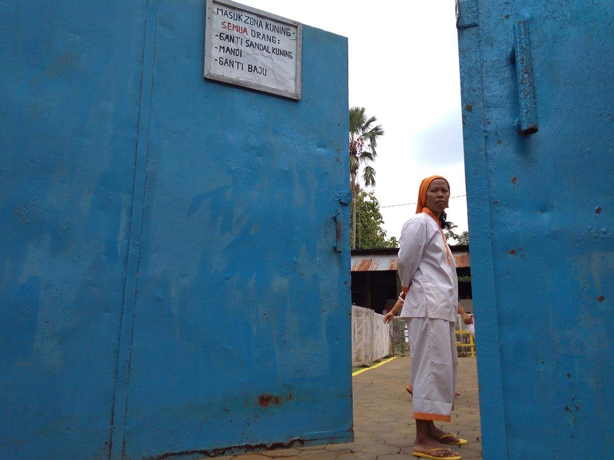 """A warning sign saying """"Entering the yellow zone, everyone must: change into yellow slippers, take a shower, change clothes"""" is put on the iron gate. JP/Ganug Nugroho Adi"""
