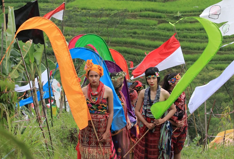 Participants of the Mount Lawu Flag Festival walk up a hill in Gerdu village, Karanganyar regency, Central Java.