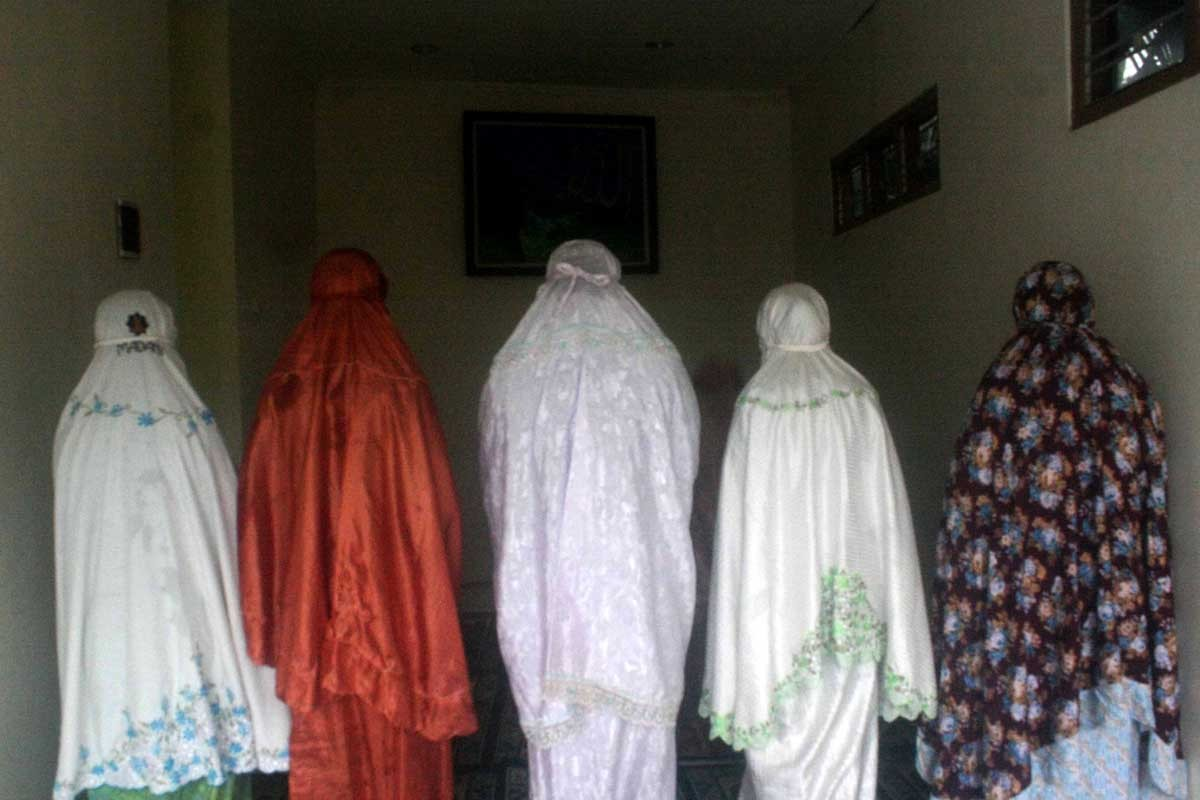 Five female soccer players pray before the match. JP/Maksum Nur Fauzan