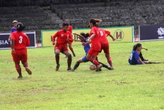 Players from both teams fight over the ball. JP/Maksum Nur Fauzan