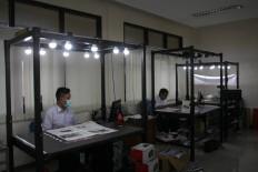 Work in progress: Three employees digitize old newspapers. JP/Maksum Nur Fauzan.