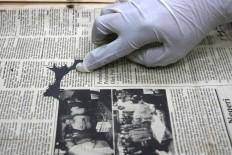 Missing piece: An employee shows a damaged newspaper. JP/Maksum Nur Fauzan.