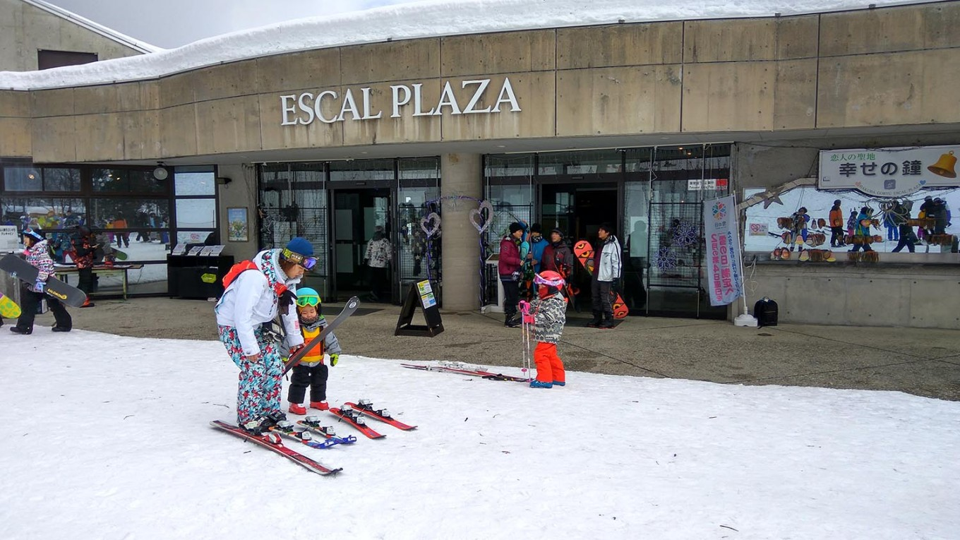 A mother helps her children strap on skis in front of Escal Plaza, the main hall of Hakuba Goryu Snow Resort. Escal Plaza offers skiing classes as well as rental services for skiing gear. JP/Agnes Anya