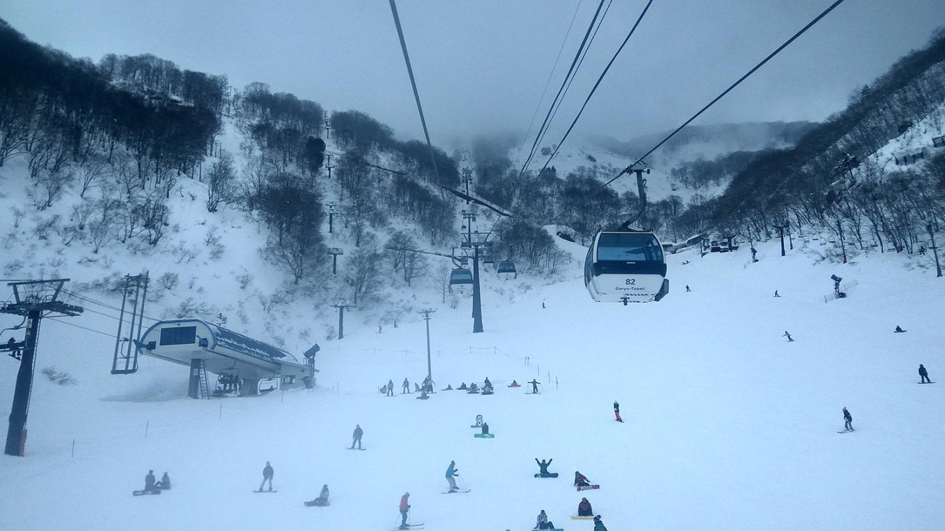 Goryu-Toomi cable cars travel above visitors skiing on Toomi slope. The area, suitable for beginners and families, opens at 6:30 a.m. and operates until 9:30 p.m. JP/Agnes Anya