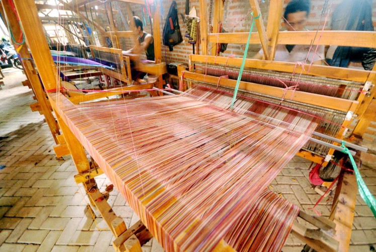 Gender equality: Men work with manual weaving looms in Bandar Kidul subdistrict, Kediri, East Java.