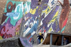 A picture taken on December 16, 2017 shows children skateboarding next to graffiti murals in the Jordanian capital Amman. A tiny group of graffiti artists are on a mission -- daubing flowers, faces and patterns across the capital Amman to bring more colour to the lives of its four million inhabitants.