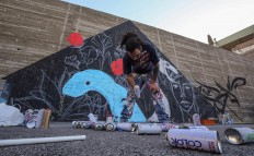 Suhaib Attar, a 25-year-old graffiti artist and student, picks up a canister of spray paint as he draws a mural on a wall in the capital Jordanian Amman on December 16, 2017. A tiny group of graffiti artists are on a mission -- daubing flowers, faces and patterns across the capital Amman to bring more colour to the lives of its four million inhabitants.