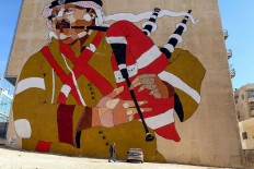 A picture taken on December 17, 2017 shows a graffiti mural on a wall in the Jordanian capital Amman. A tiny group of graffiti artists are on a mission -- daubing flowers, faces and patterns across the capital Amman to bring more colour to the lives of its four million inhabitants. In a conservative society like Jordan's, the graffiti artists have constantly had to challenge convention to carve out a niche for their works, though still with limits as they steer away from politics and religion. AFP/Khalil Mazraawi