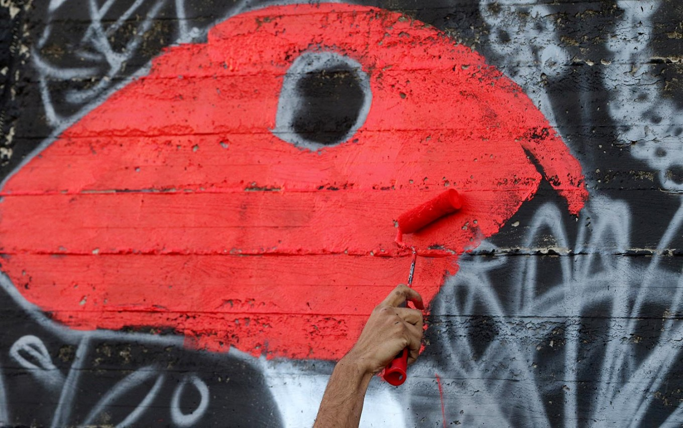 A picture taken on December 16, 2017 shows a graffiti artist drawing a mural in the Jordanian capital Amman. A tiny group of graffiti artists are on a mission -- daubing flowers, faces and patterns across the capital Amman to bring more colour to the lives of its four million inhabitants. In a conservative society like Jordan's, the graffiti artists have constantly had to challenge convention to carve out a niche for their works, though still with limits as they steer away from politics and religion. AFP/Khalil Mazraawi
